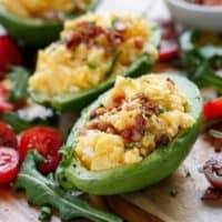 Cheesy Scrambled Eggs in Avocado With Crispy Bacon Pieces | https://cafedelites.com