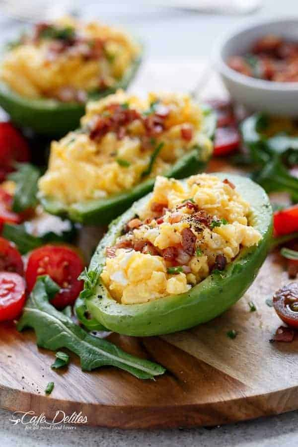 Cheesy Scrambled Eggs in Avocado With Crispy Bacon Pieces | https://cafedelites.com