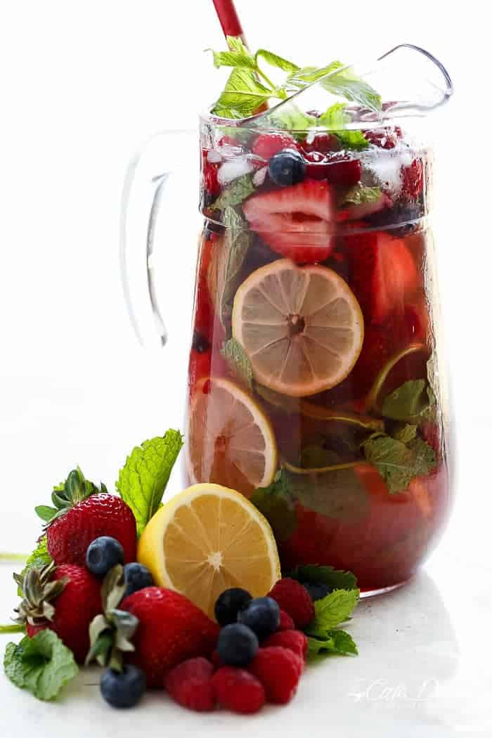 A beautiful and refreshing spin on a traditional sangria using a mixture of frozen berries for a full berry flavour, a simple to make strawberry syrup, and the sweet Italian tangy-sweet citrus from limoncello! | https://cafedelites.com