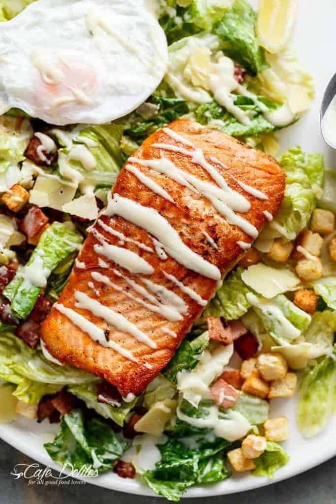Crispy pan fried Salmon meets Caesar salad for a twist on the traditional! Easy to make with creamy avocado slices, crunchy croutons, the tang of shaved parmesan cheese, a perfect runny poached egg on top and a lightened up Caesar dressing!| https://cafedleites.com