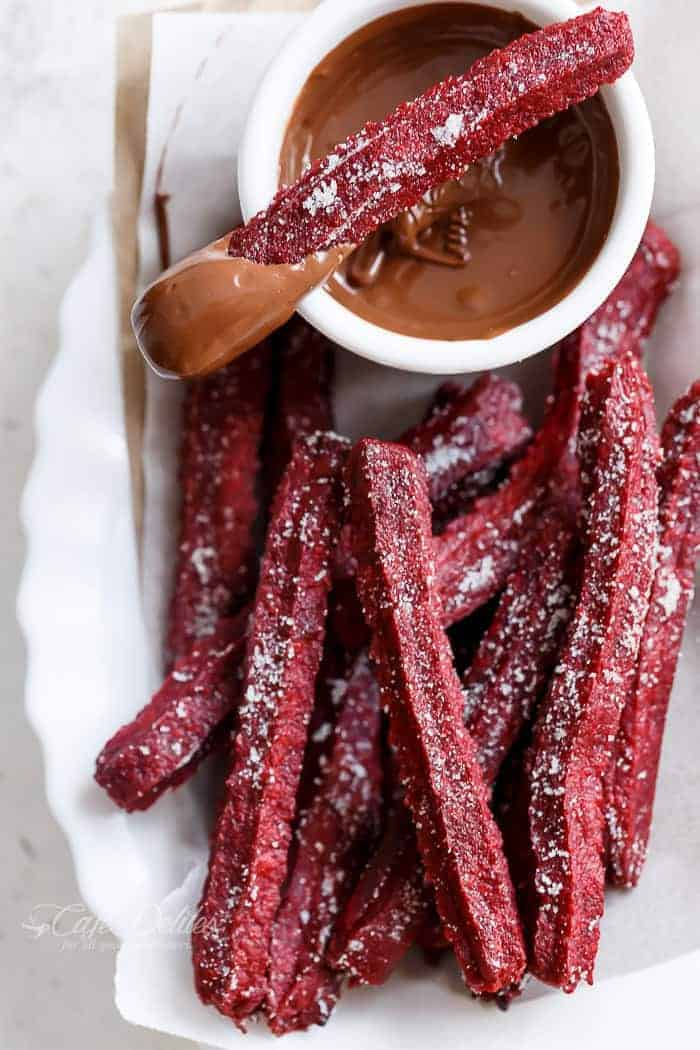 The Best Red Velvet Churros... now you can make them at home with a Red Velvet Twist! Just like store-bought Churros. BUT BAKED not fried and only 36 calories EACH! | https://cafedelites.com