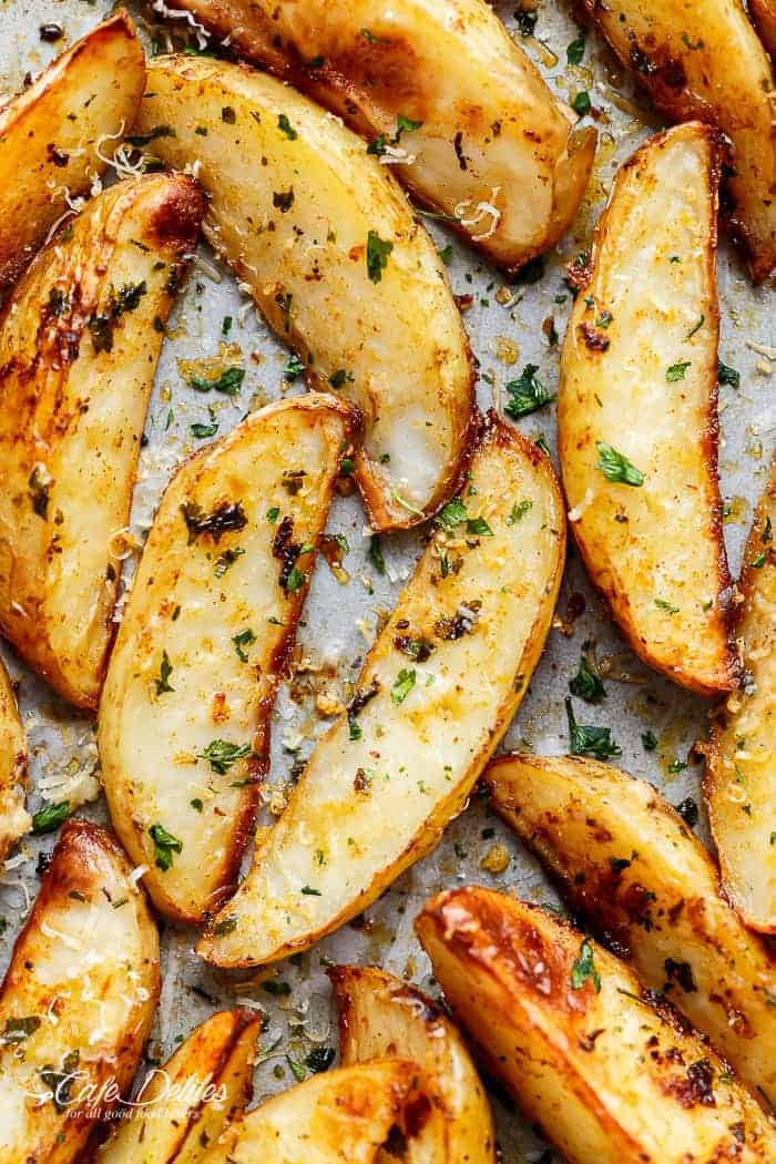 Crispy Garlic Baked Potato Wedges are soft pillows on the inside, and crunchy on the outside with a good kick of garlic and parmesan cheese! | https://cafedelites.com