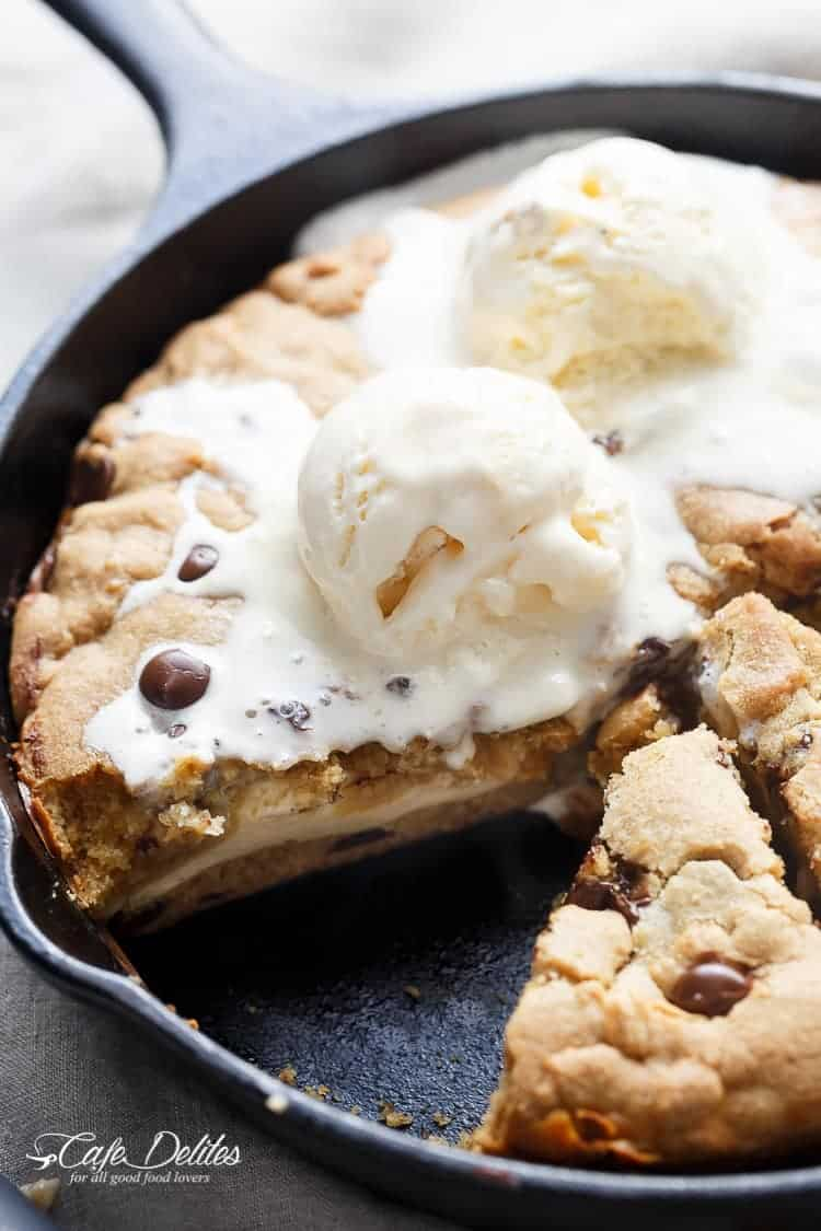 A crispy, soft Cheesecake Stuffed Chocolate Chip Skillet Cookie! Layers of cookie dough and cheesecake is the ultimate dessert for cheesecake/cookie lovers! | https://cafedelites.com