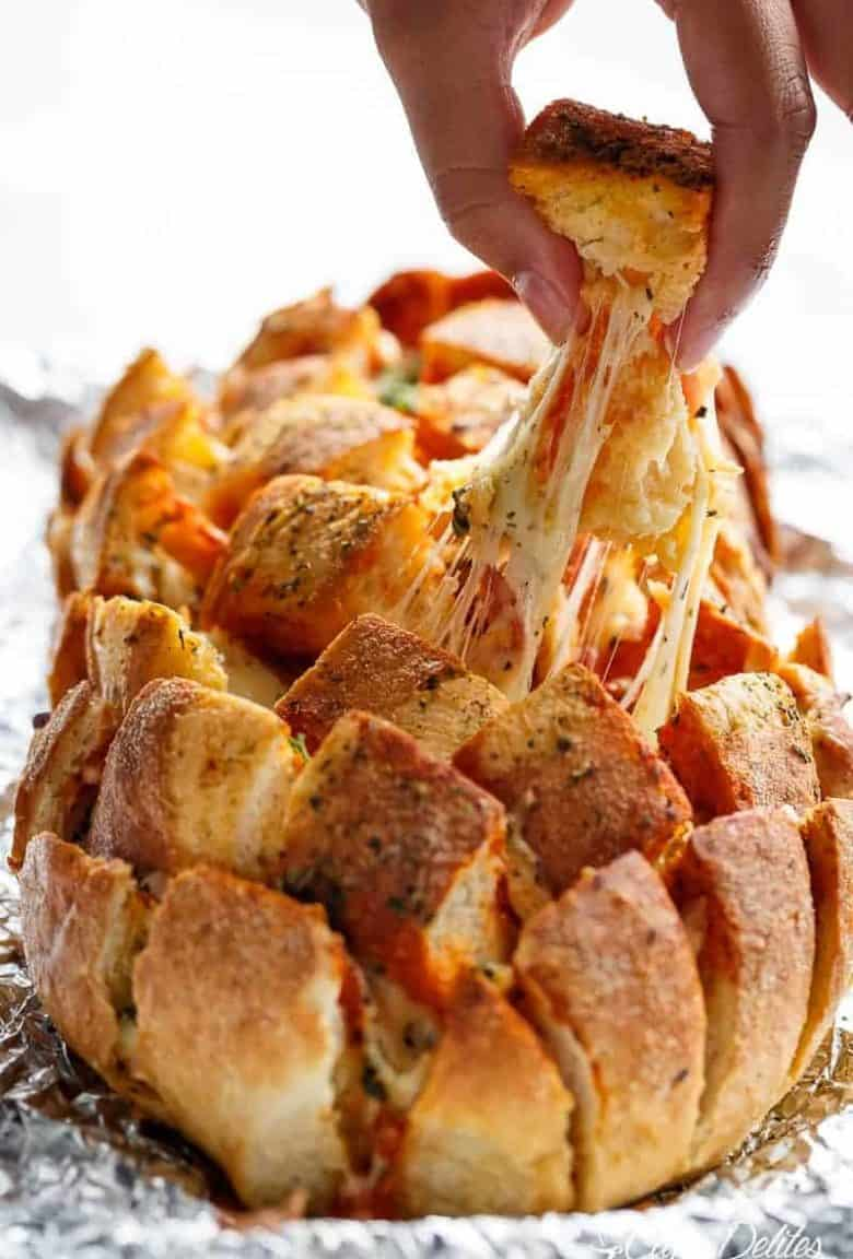 This Garlic Butter Pizza Pull Apart Bread is smothered in garlic butter, stuffed with pizza fillings, and topped with so.much.cheese! | https://cafedelites.com