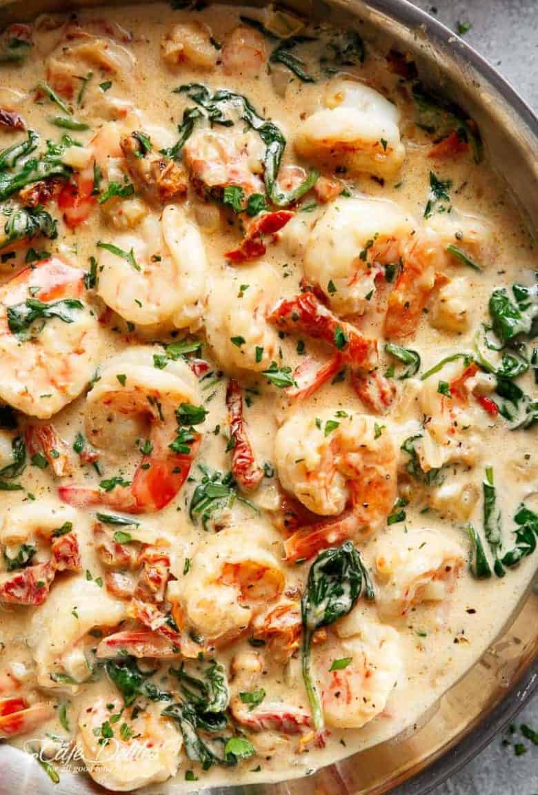 Creamy Garlic Butter Tuscan Shrimp coated in a light and creamy sauce filled with garlic, sun dried tomatoes and spinach! Packed with incredible flavours! | https://cafedelites.com