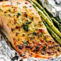 Lemon Parmesan Salmon & Asparagus Foil Packs are so easy to make, and are packed with flavour! Baked OR grilled right on your barbecue!   https://cafedelites.com
