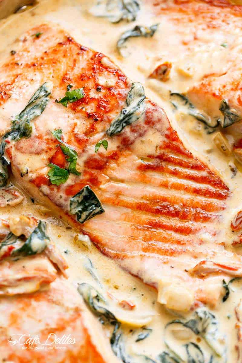Creamy Garlic Butter Tuscan Salmon (OR TROUT) is such an incredible recipe! A close up of a piece of salmon in the creamy Tuscan style sauce garnished with parsley. | https://cafedelites.com