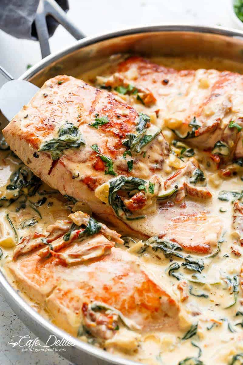 A silver spatula picks up a fillet of salmon simmered in a Creamy Tuscan style sauce with wilted spinach, sun dried tomato strips and basil strips. Salmon is presented in a silver frying pan against a white background | https://cafedelites.com