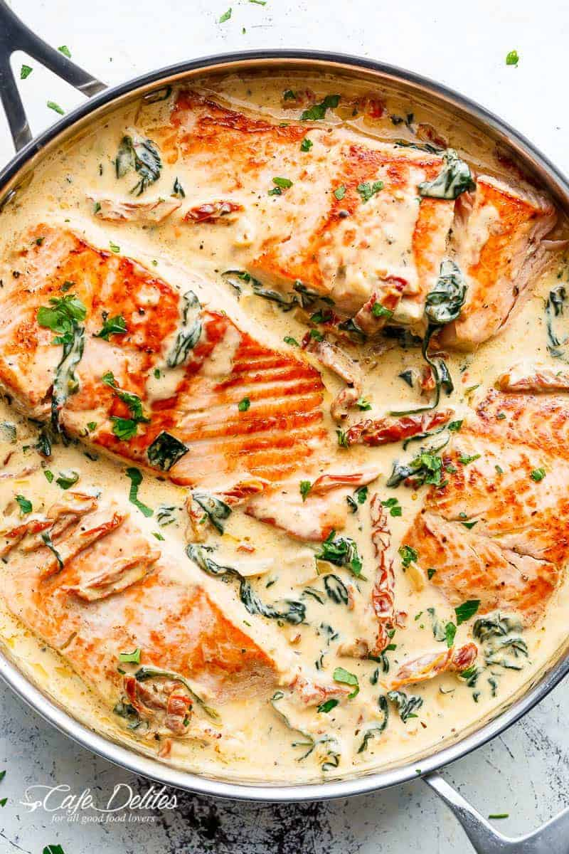 4 Salmon (OR TROUT) fillets seared in a silver frying pan, in a delicious creamy Tuscan sauce with sun dried tomatoes and wilted spinach, garnished with chopped parsley or basil. | https://cafedelites.com