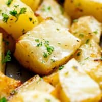 Crispy Garlic Roasted Potatoes are a super simple side dish perfect with anything! Buttery, garlicky, fluffy inside and and crispy edges. These potatoes tick all my boxes! No need for bowls or pans when you can prepare AND cook your potatoes on ONE PAN!   cafedelites.com
