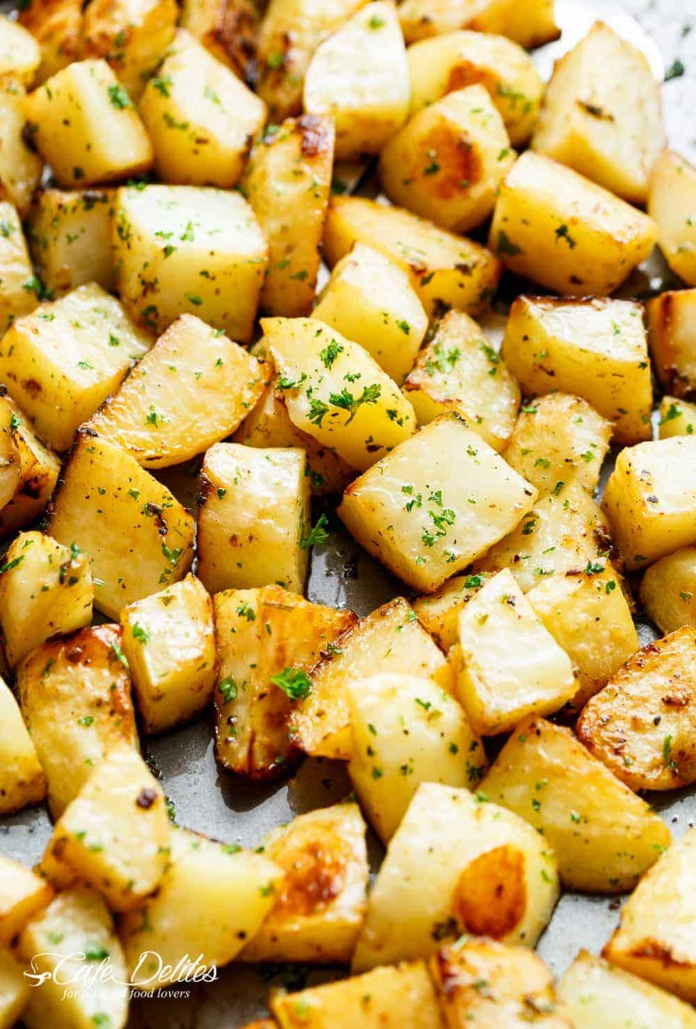 Crispy Garlic Roasted Potatoes are a super simple side dish perfect with anything! Buttery, garlicky, fluffy inside and and crispy edges. These potatoes tick all my boxes! No need for bowls or pans when you can prepare AND cook your potatoes on ONE PAN! | cafedelites.com
