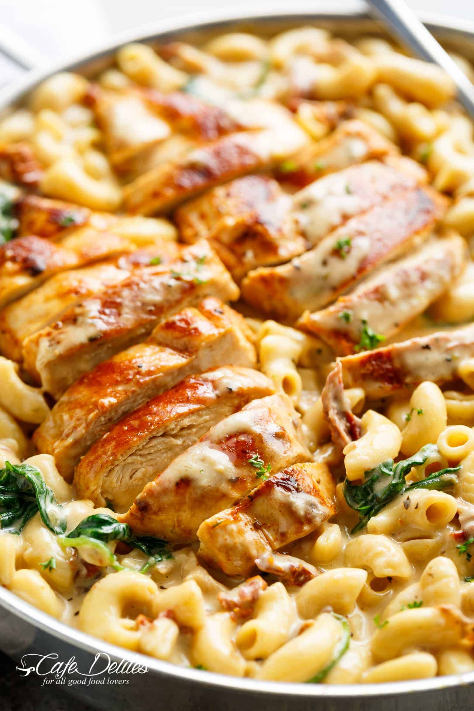 A silver frying pan filled with creamy tuscan style Mac and cheese with wilted spinach and sun dried tomato strips! Two sliced chicken breasts sit on top of Mac and cheese with a serving spoon in the pan ready to serve!