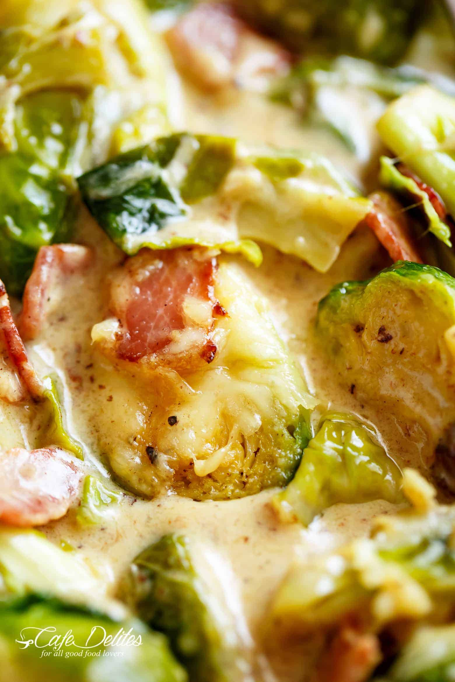 A close up of Brussel Sprouts in a cheesy cream sauce with crispy bacon pieces.