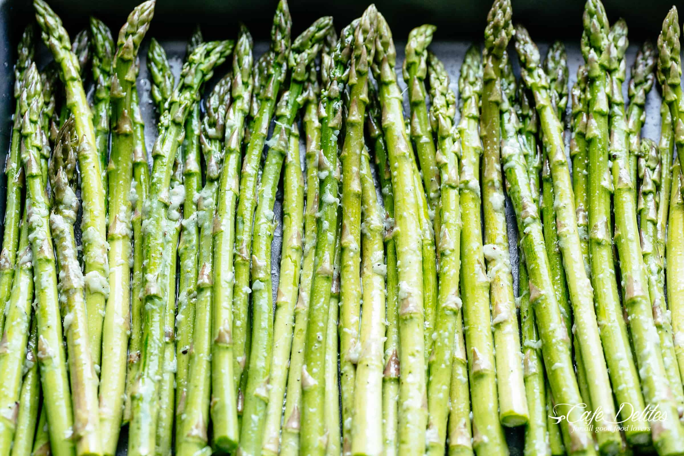 How To Roast Asparagus spears on a dark grey/silver baking sheet | cafedelites.com