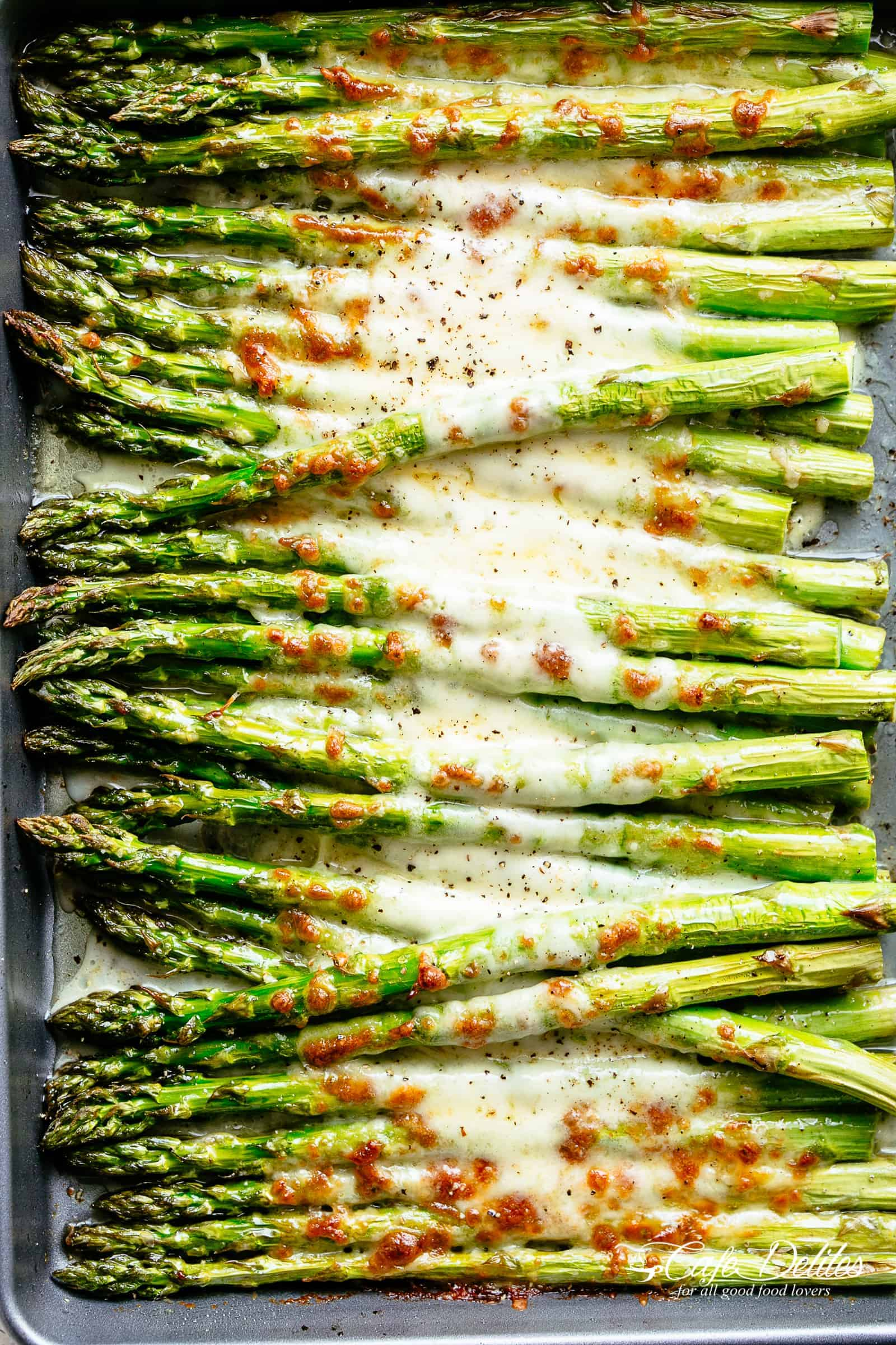 Cheesy Garlic Roasted Asparagus with mozzarella cheese on a silver/grey baking sheet. Low Carb, Keto AND the perfect way to get your veggies in! Even non-asparagus fans LOVE this recipe! Tastes so amazing that the whole family gets behind this asparagus recipe | cafedelites.com