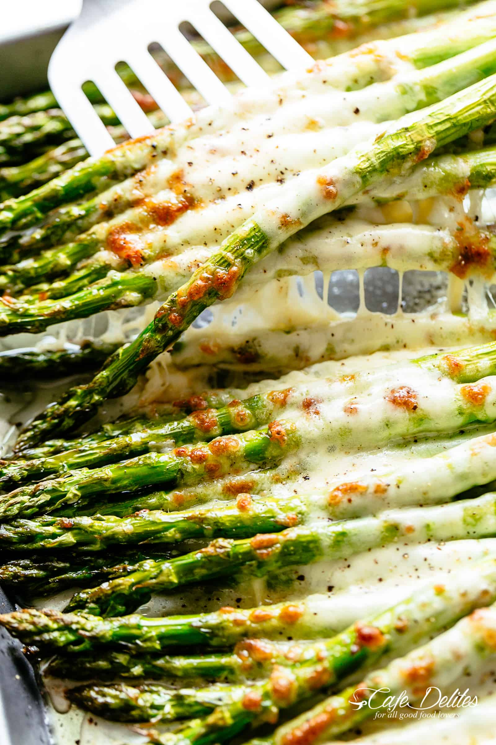 A silver spatula picks up a pile of six roasted asparagus spears topped with melted mozzarella cheese | cafedelites.com