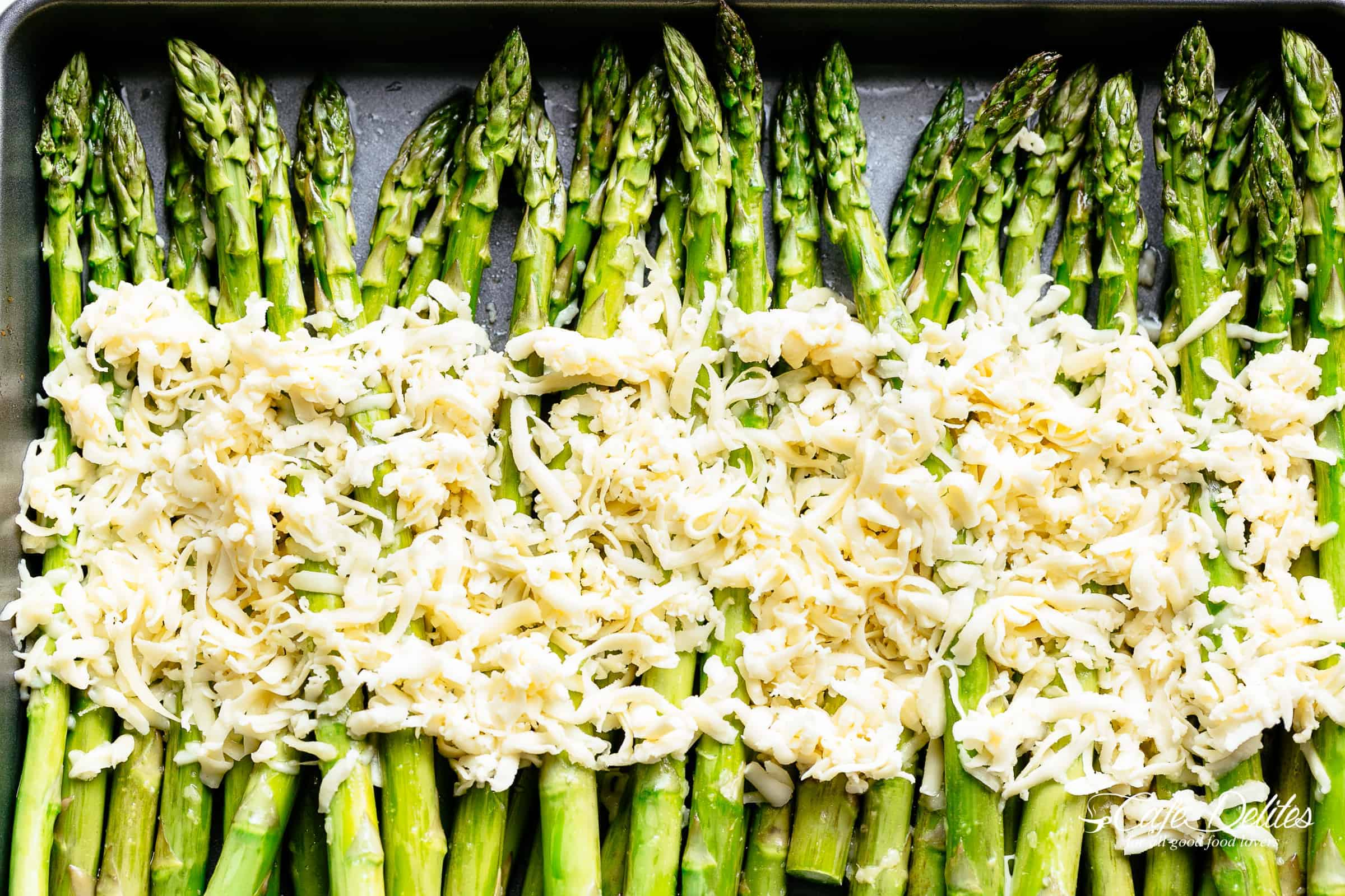 Asparagus ready for the oven with shredded mozzarella cheese! | cafedelites.com
