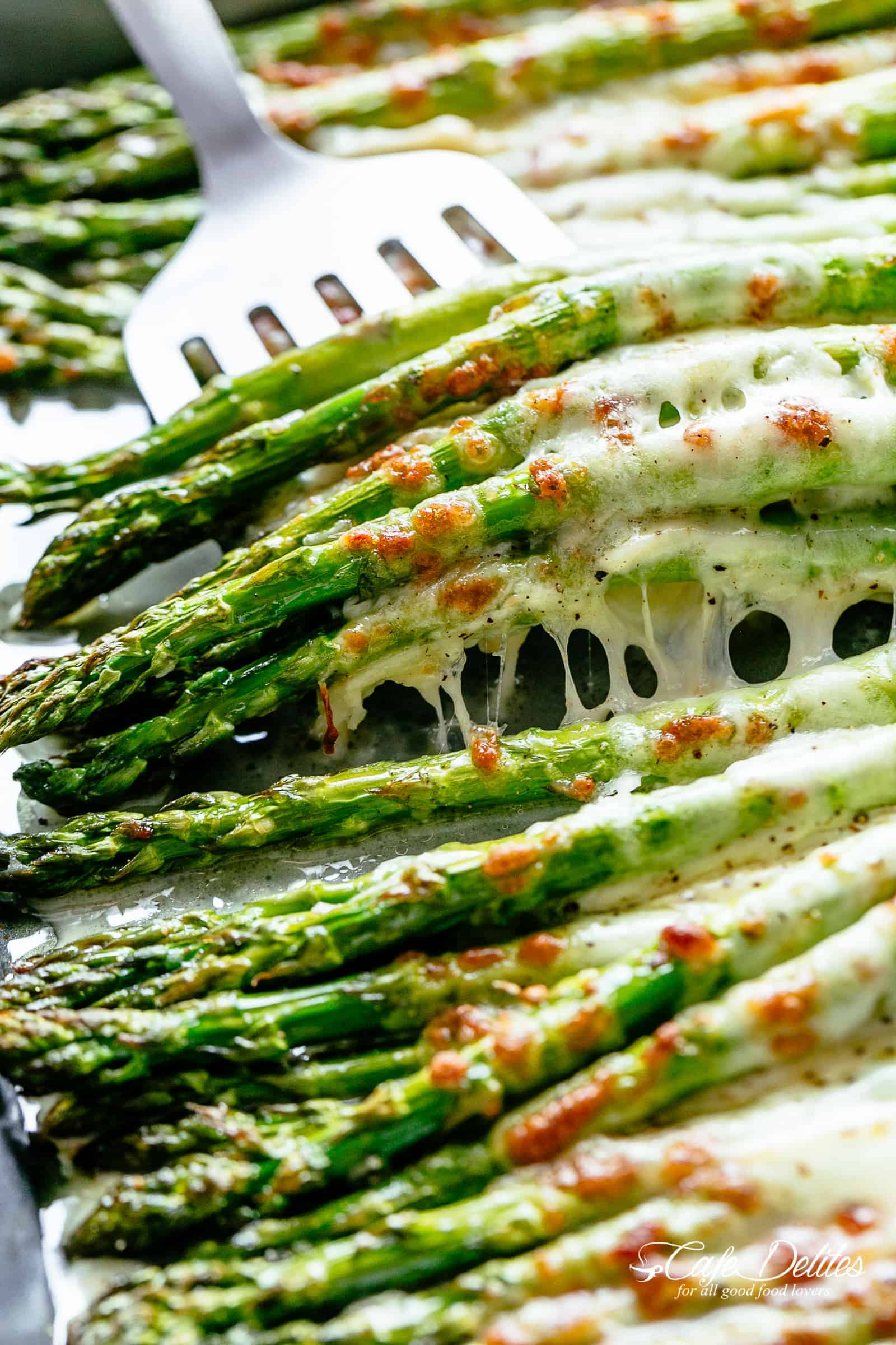 A silver spatula picks up a pile of five roasted asparagus spears topped with melted mozzarella cheese | cafedelites.com