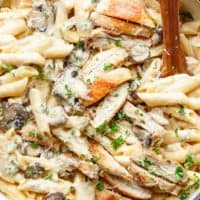 Creamy Garlic Parmesan Chicken Alfredo is all cooked in ONE POT! Ready and on the table in less than 20 minutes! Seared chicken is mixed through a super creamy garlic parmesan flavoured pasta with white wine and mushrooms! A favourite Chicken Alfredo recipe! | cafedelites.com