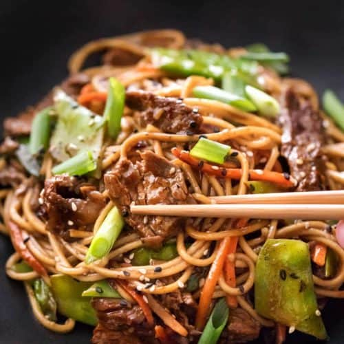 Beef stir fry in bowl with chopsticks