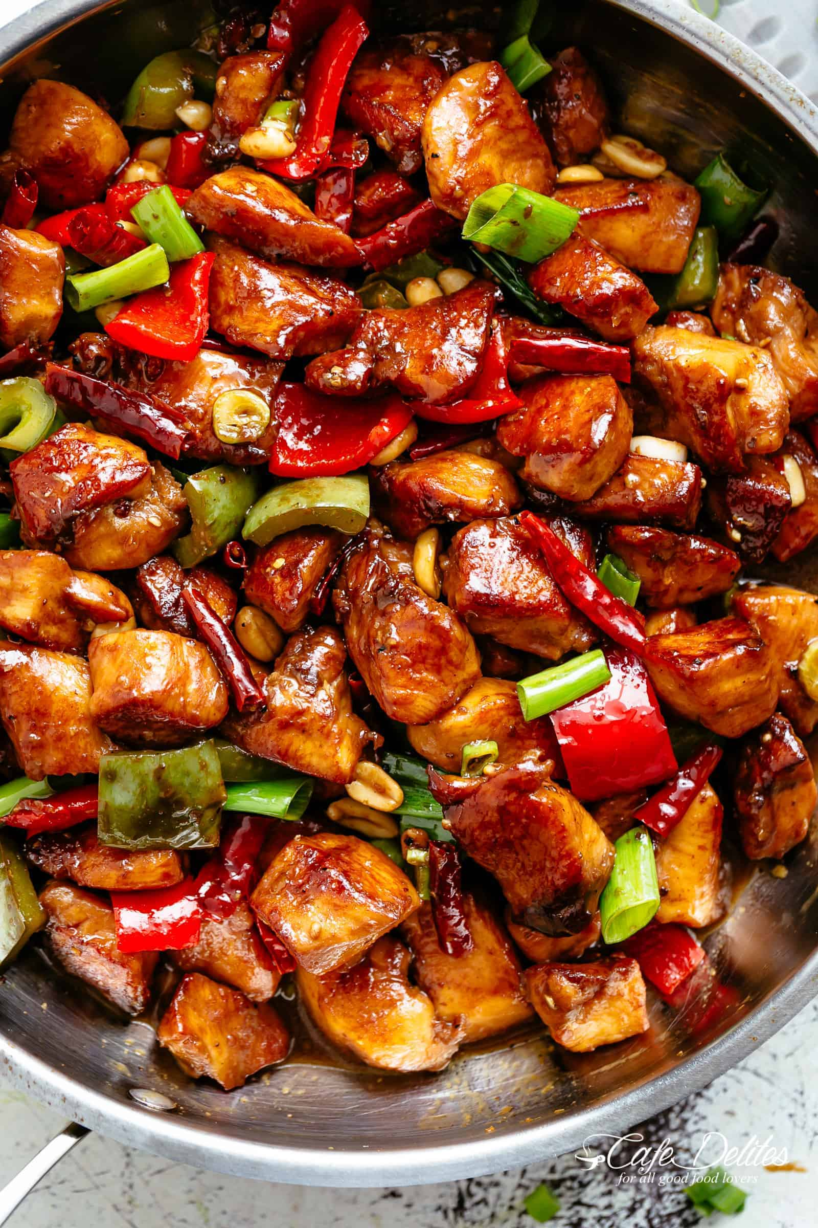 Kung Pao Chicken is highly addictive stir-fried chicken with the perfect combination of salty, sweet and spicy flavour! Make it better than Chinese take out right at home! With crisp-tender chicken pieces and some crunchy veggies thrown in, this is one Kung Pao chicken recipe hard to pass up!  | cafedelites.com