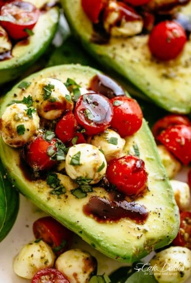 Basil Pesto Caprese Stuffed Avocado drizzledwith balsamic glaze make an incredible light lunch or snack! Take creamy avocados to a different level! Sweet and juicy grape/cherry tomatoes with fresh mozzarella balls are tossed through basil pesto and spooned into avocado halves!   cafedelites.com