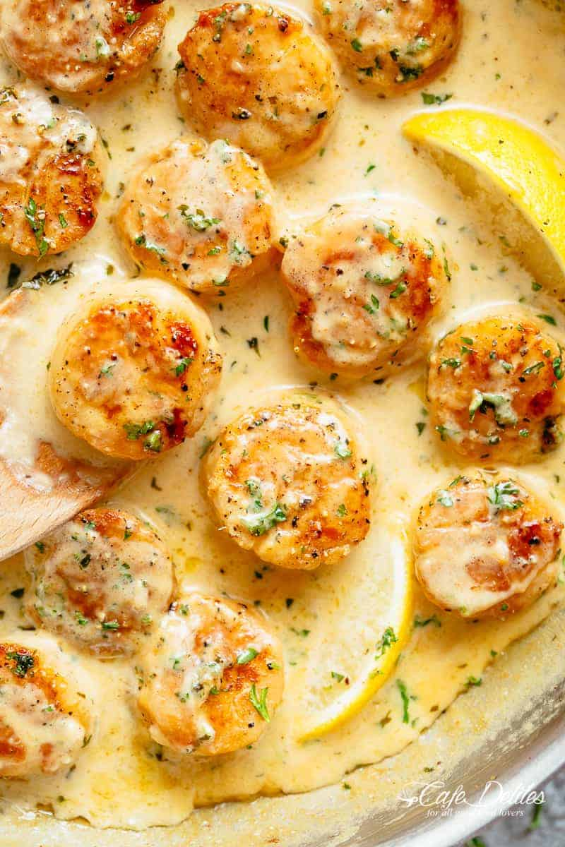 Creamy Garlic Scallops are just as good as restaurant scallops with minimal ingredients and maximum flavour! A silky, creamy garlic sauce with a hint of lemon coats crispy, buttery scallops! With only a handful of ingredients, you're minutes away from having the most incredible scallops on your dinner table! | cafedelites.com