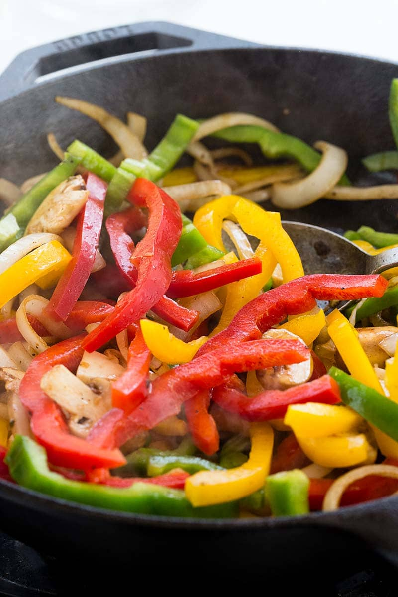 Yellow, green, and red bell peppers cooking in a skillet