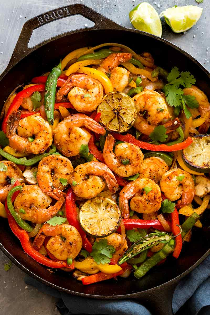 spicy shrimp fajitas cooking in a cast iron skillet