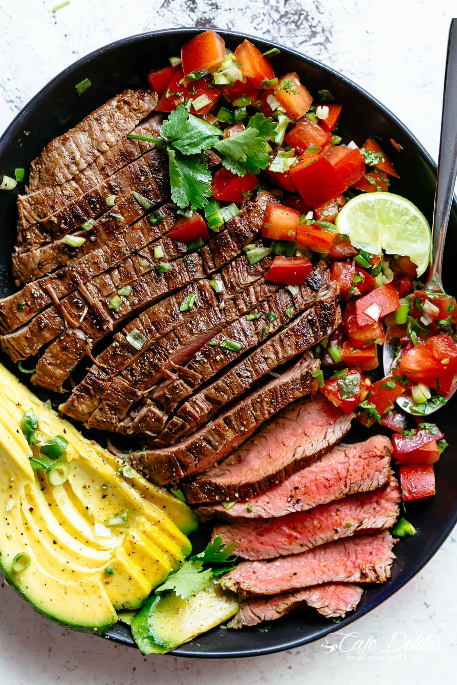 Carne Asada prepared with a deliciously easy and authentic marinade just in time for your Cinco De Mayo menu planning! Juicy and tender grilled flank or skirt steak full of incredible Mexican flavours makes this homemade Carne Asada recipe better than any restaurant! | cafedelites.com