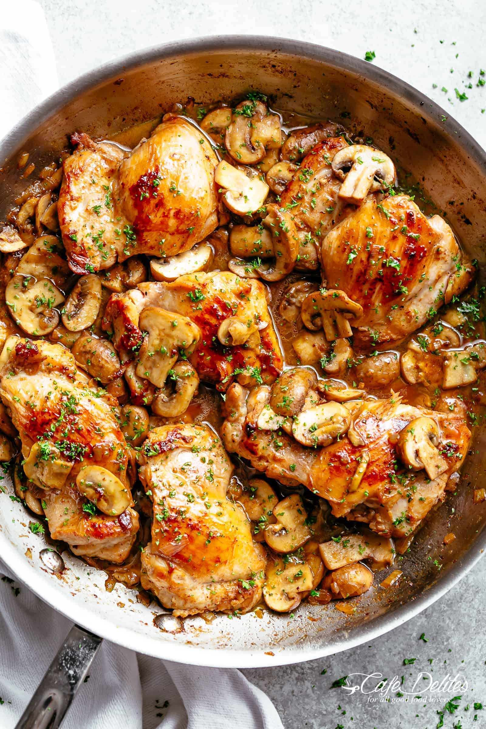 Golden seared Garlic Mushroom Chicken Thighs in a delicious, buttery sauce with a sprinkle of herbs | cafedelites.com