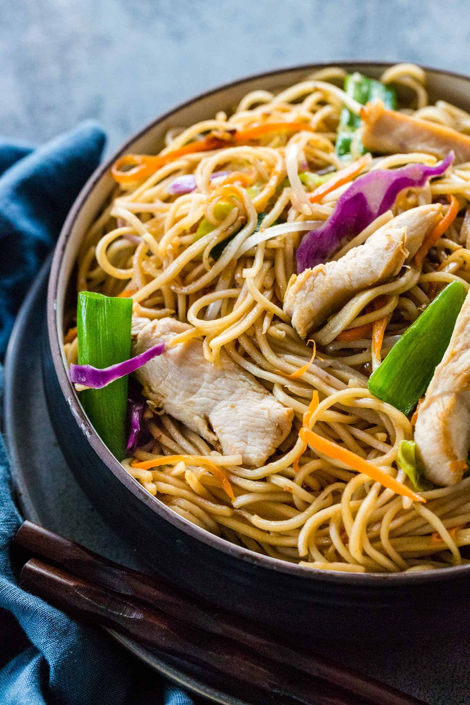 chicken chow mein served in a dark bowl