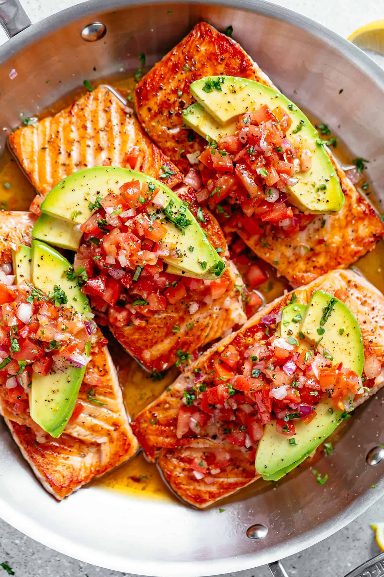 Pan Seared Salmon in a buttery garlic lemon sauce, topped with a fresh tomato salsa and avocado slices! Healthy and low carb! | cafedelites.com