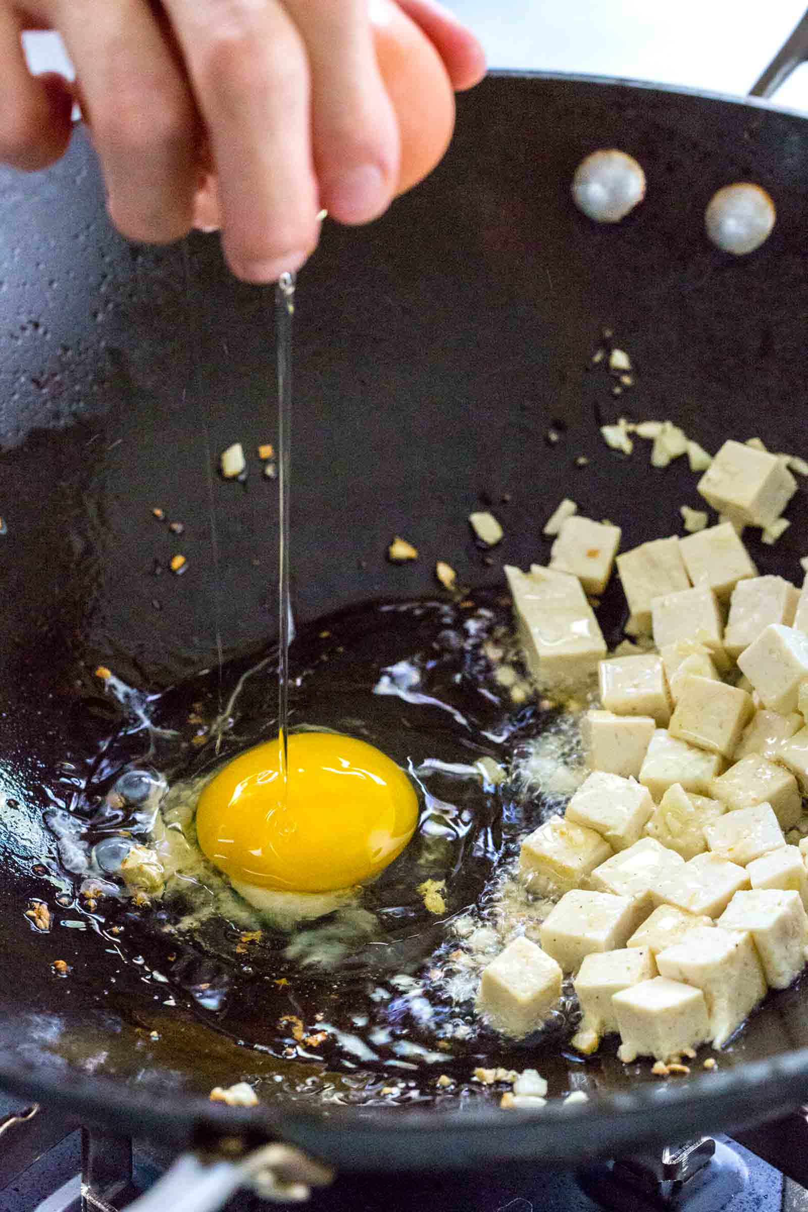 cracking an egg into a wok filled with tofu