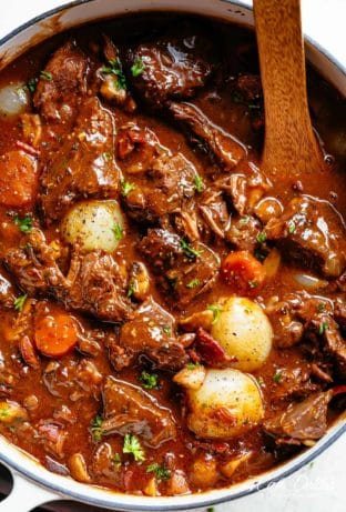 Tender fall apart chunks of beef simmered in a rich red wine gravy makes Julia Child's Beef Bourguignon an incredible family dinner. Slow Cooker, Instant Pot/Pressure Cooker, Stove Top and the traditional Oven method included! Easy to make, every step is worth it | cafedelites.com
