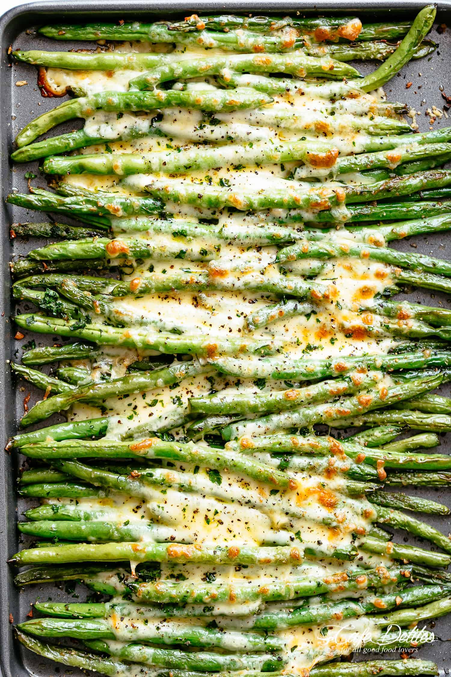 A tray of roasted green beans with melted cheese