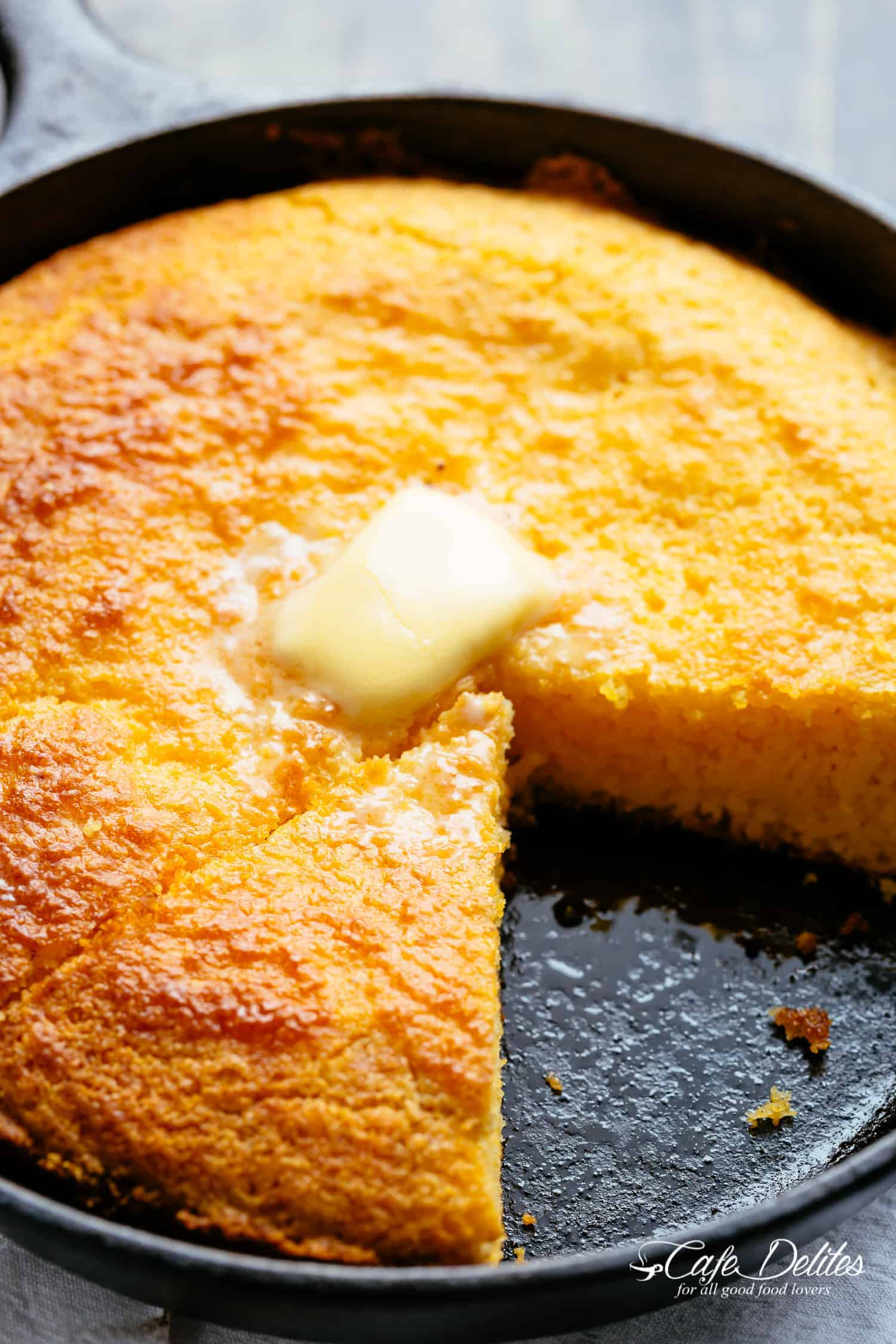 Sliced cornbread in a black skillet with butter!