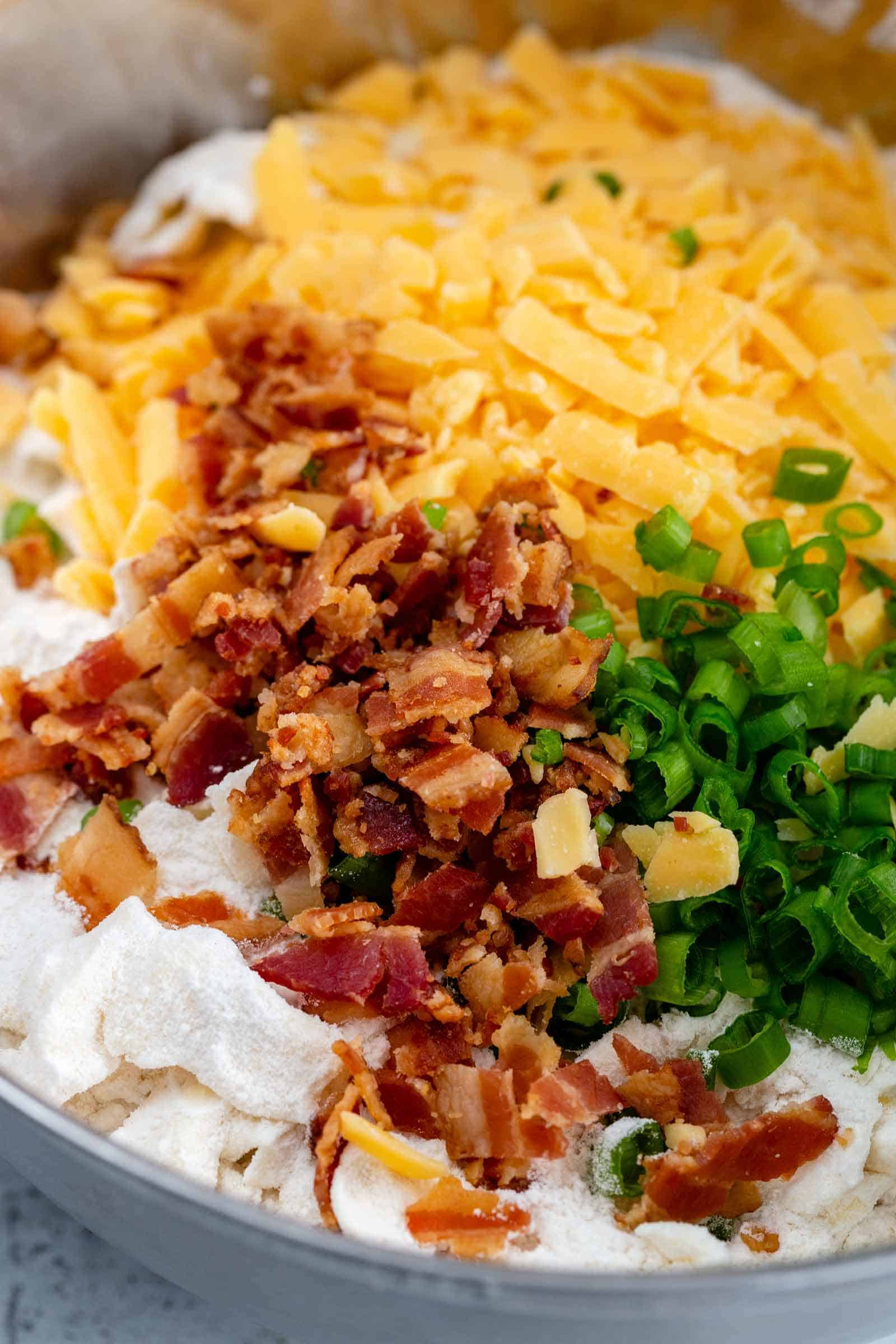 chopped bacon, grated cheddar cheese and sliced green onions in a mixing bowl