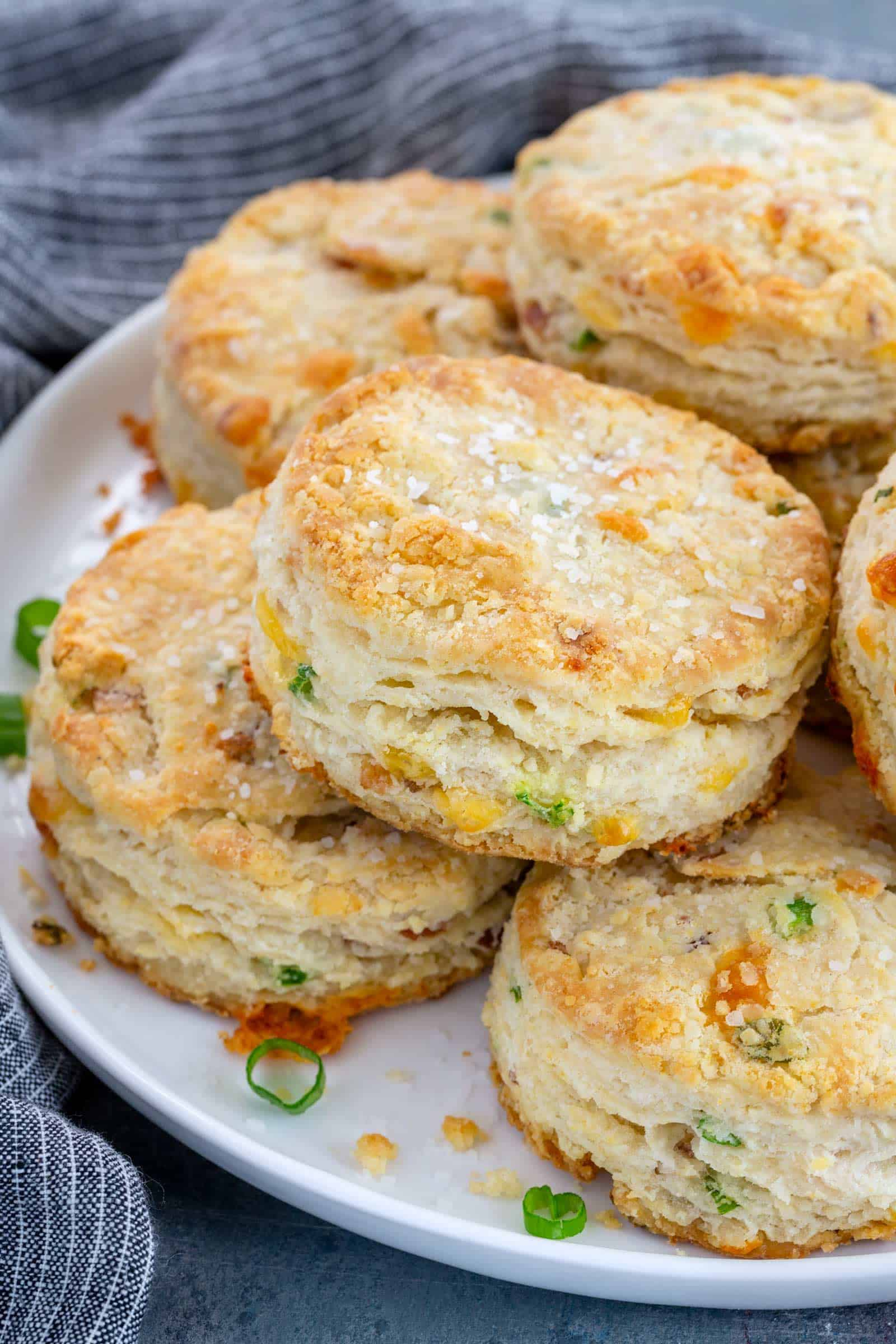 bacon cheddar biscuits stacked on a white plate