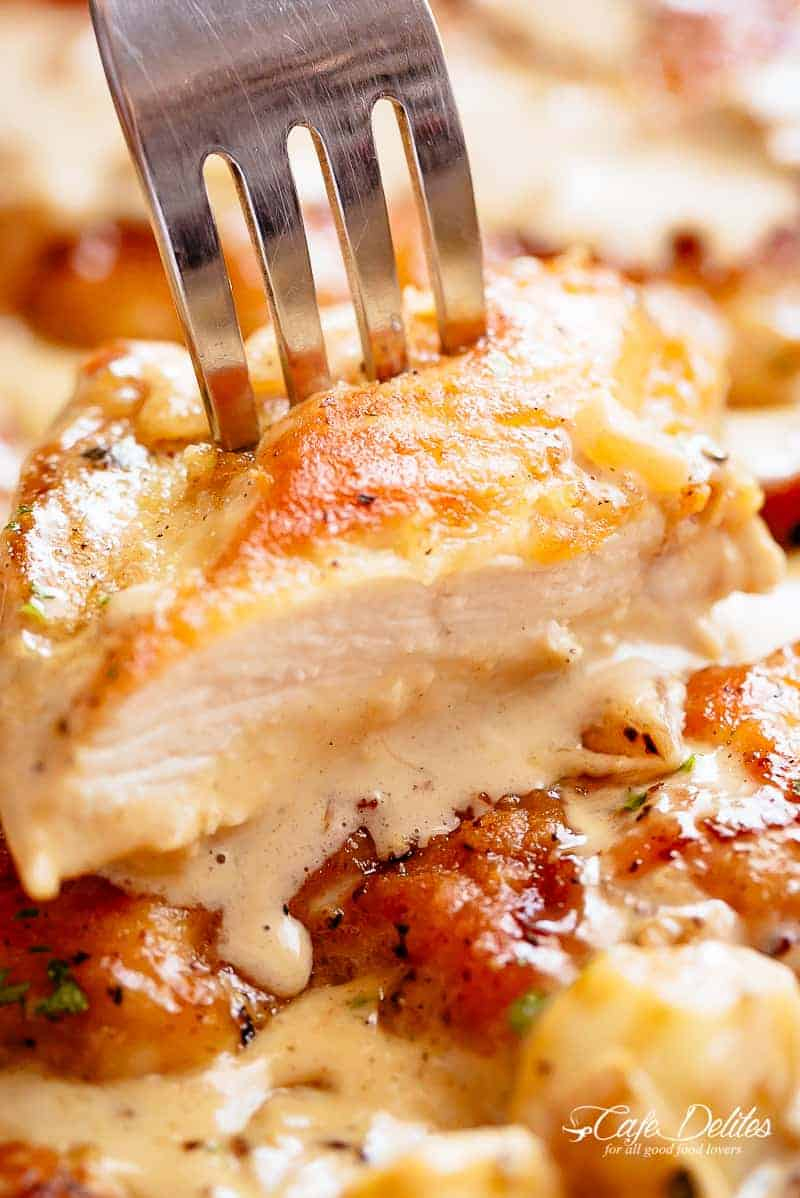 Chicken breasts are pan fried in until golden and crispy before being added to a mouth-watering garlic cream sauce! A silver fork pierces through a sliced piece of chicken! | cafedelites.com