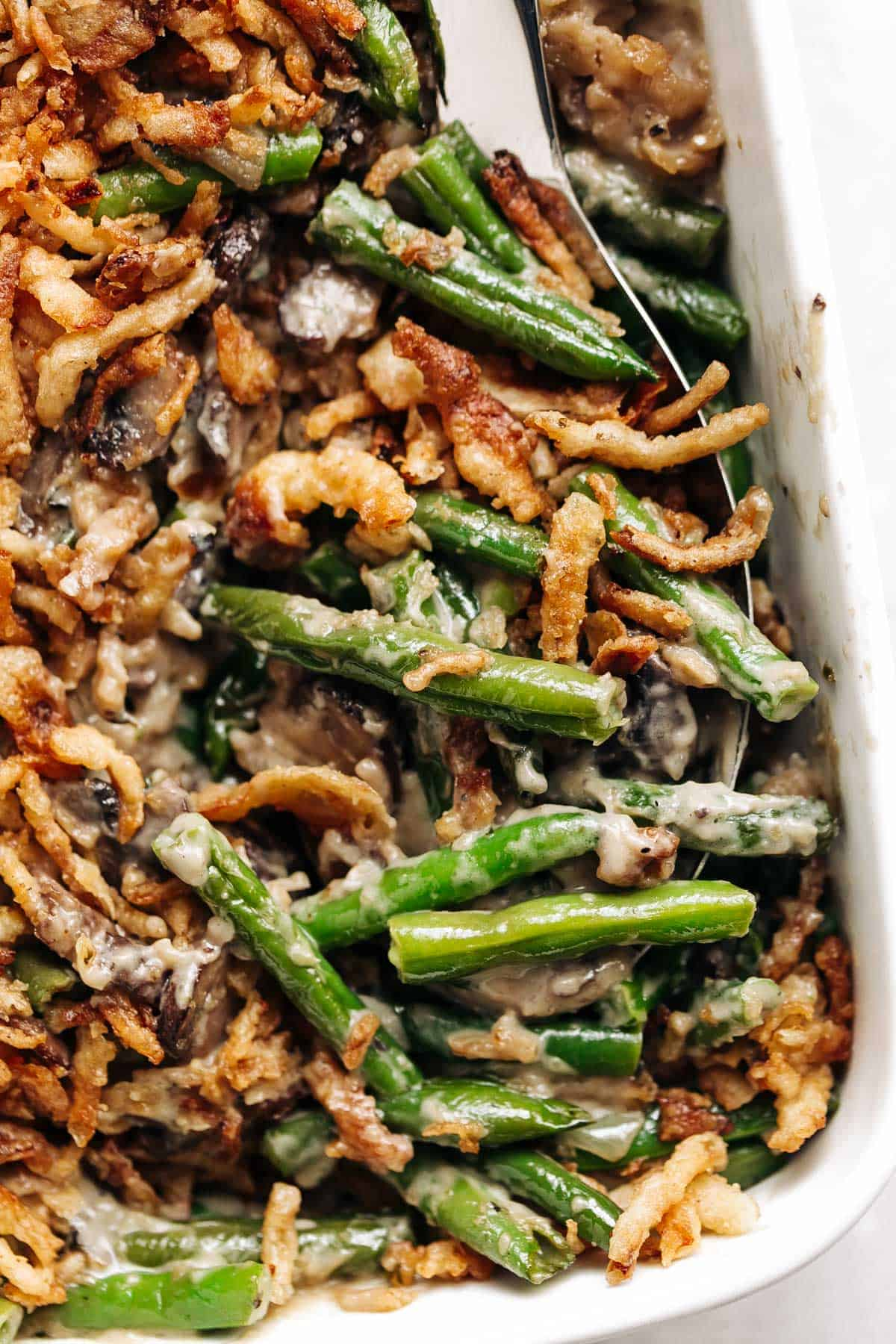 A ladle of green bean casserole fresh in a baking dish.