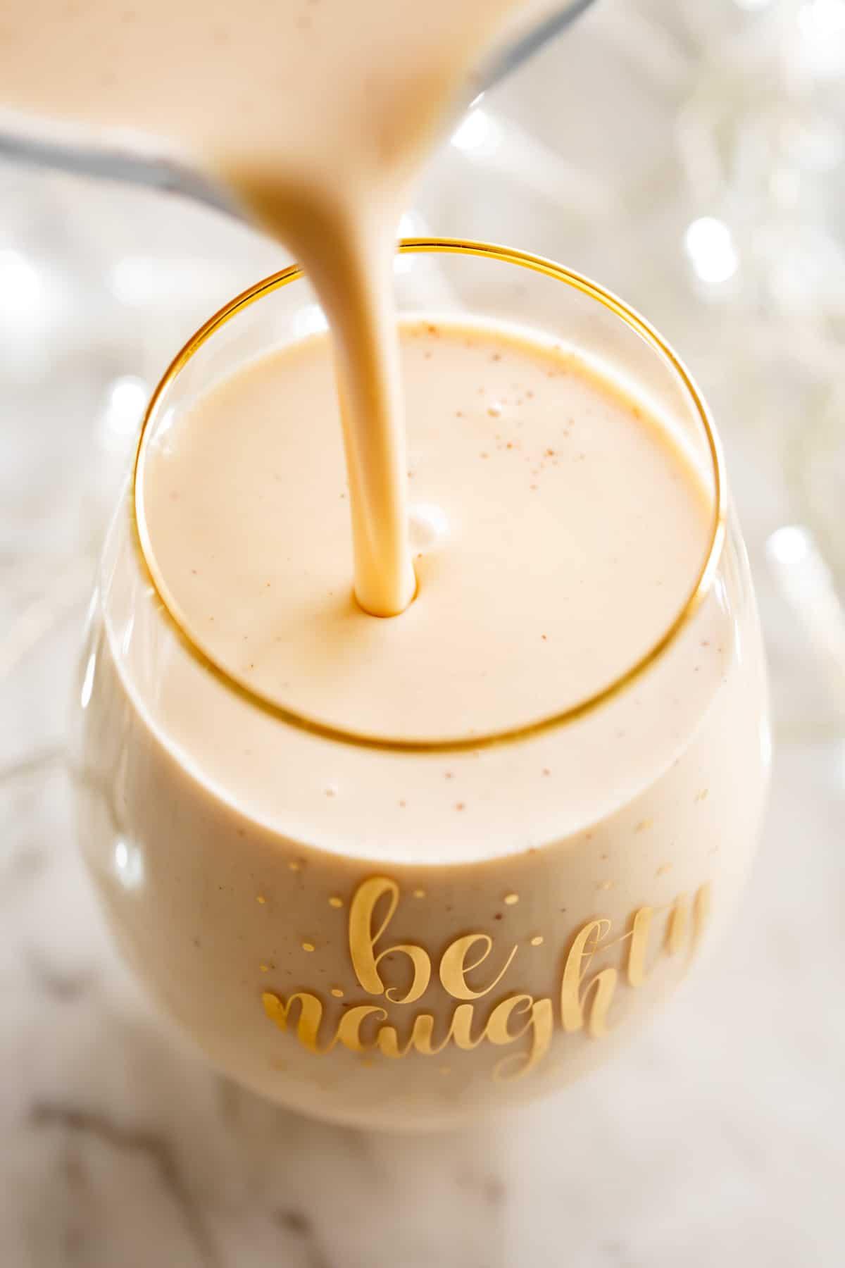 pouring eggnog into a glass cup | cafedelites.com