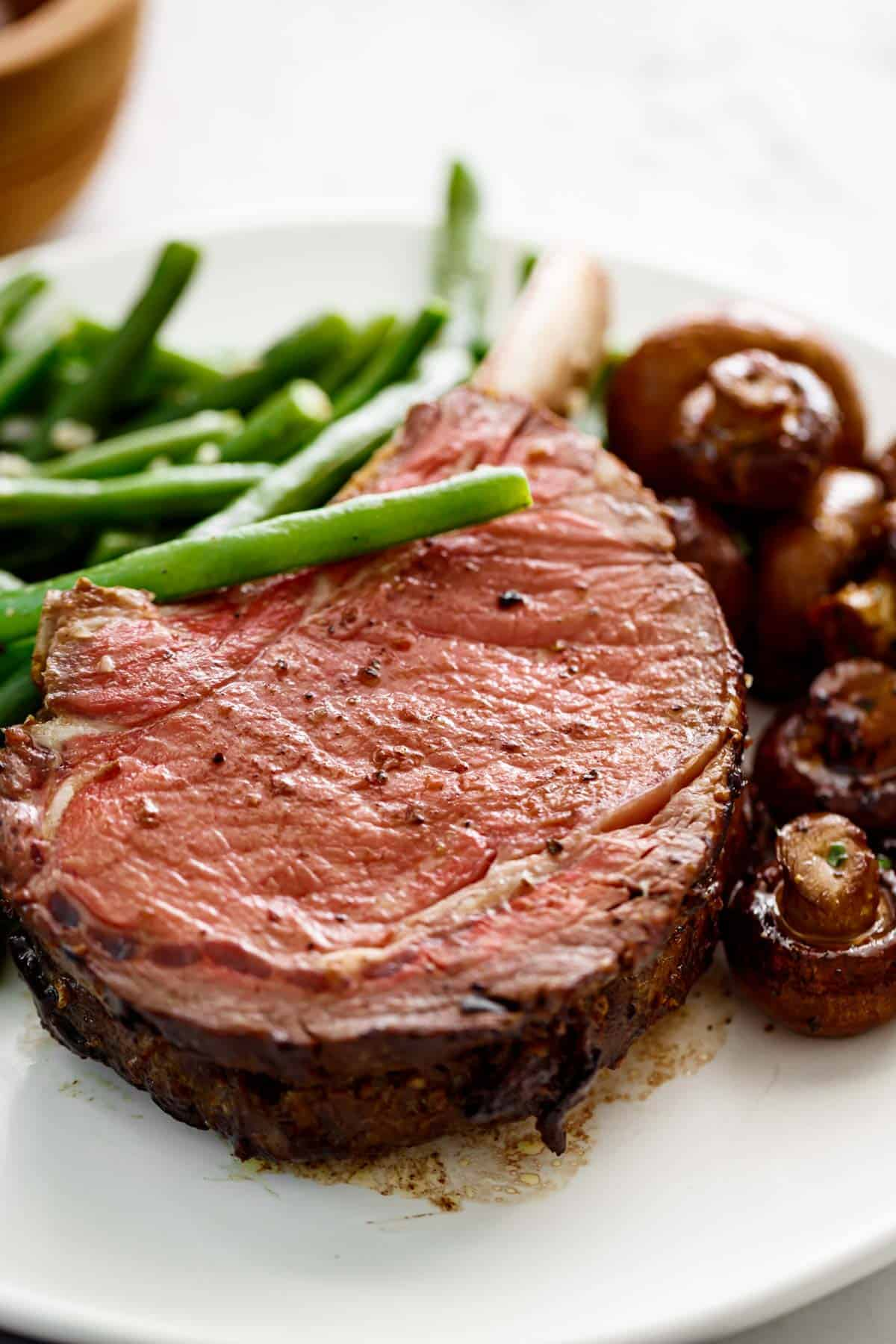 Prime Rib with garlic butter served with green beans and mushrooms | cafedelites.com