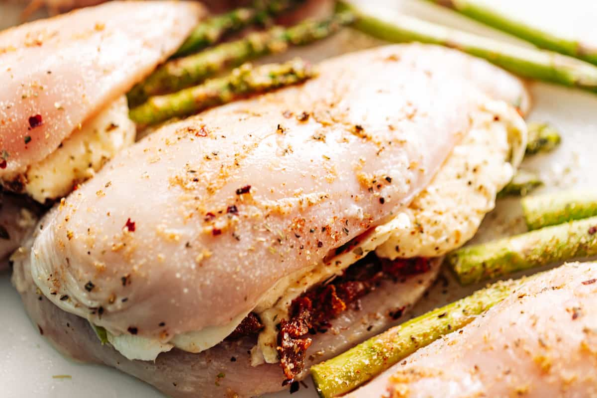 Raw stuffed chicken breasts with asparagus, mozzarella cheese and sun dried tomato strips on a white cutting board.