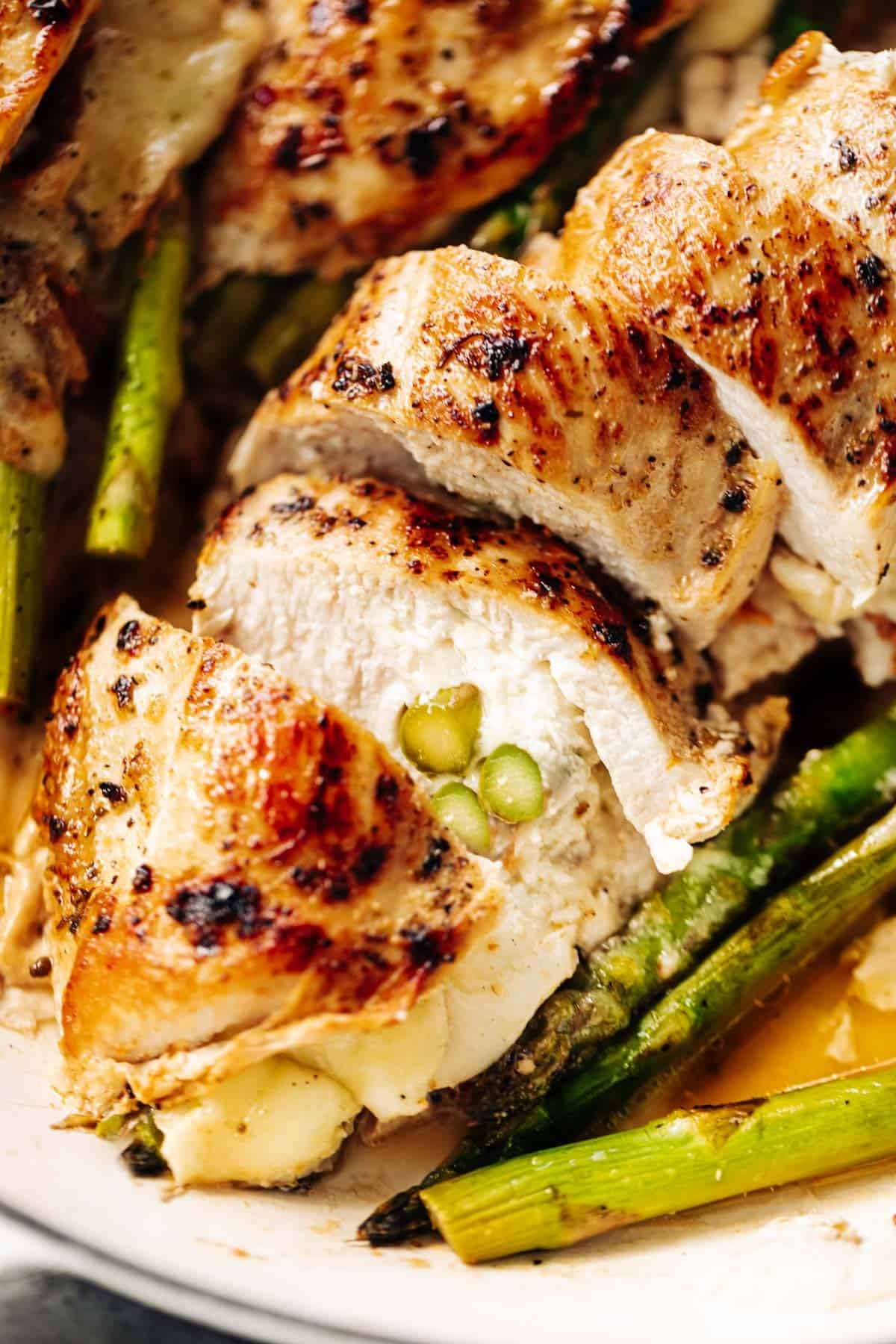 A close up image of one asparagus and mozzarella cheese stuffed chicken breast sliced open to see the inside | cafedelites.com
