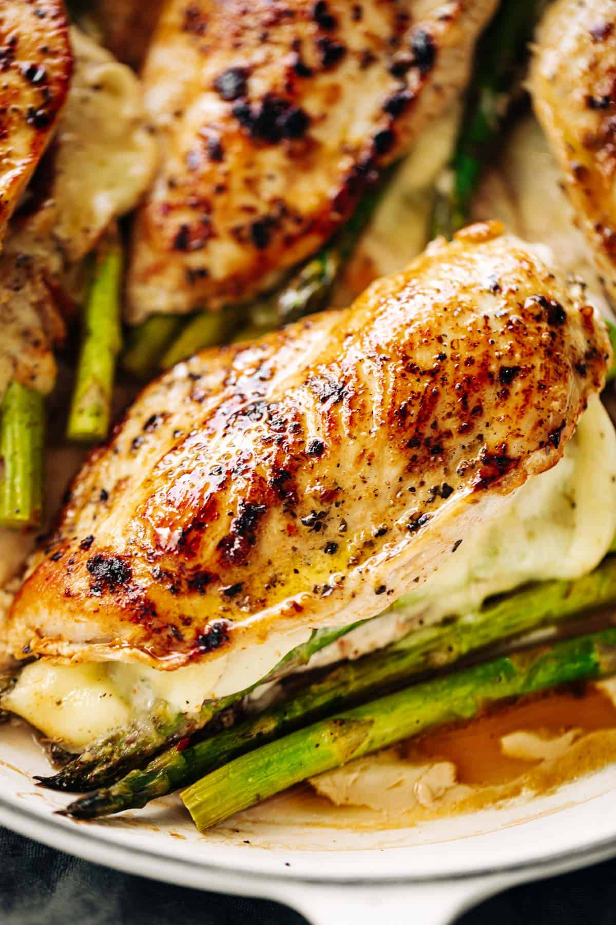 Four asparagus and mozzarella cheese stuffed chicken breasts in a white casserole dish | cafedelites.com