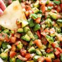 A bowl of avocado salsa with a tortilla chip | cafedelites.com