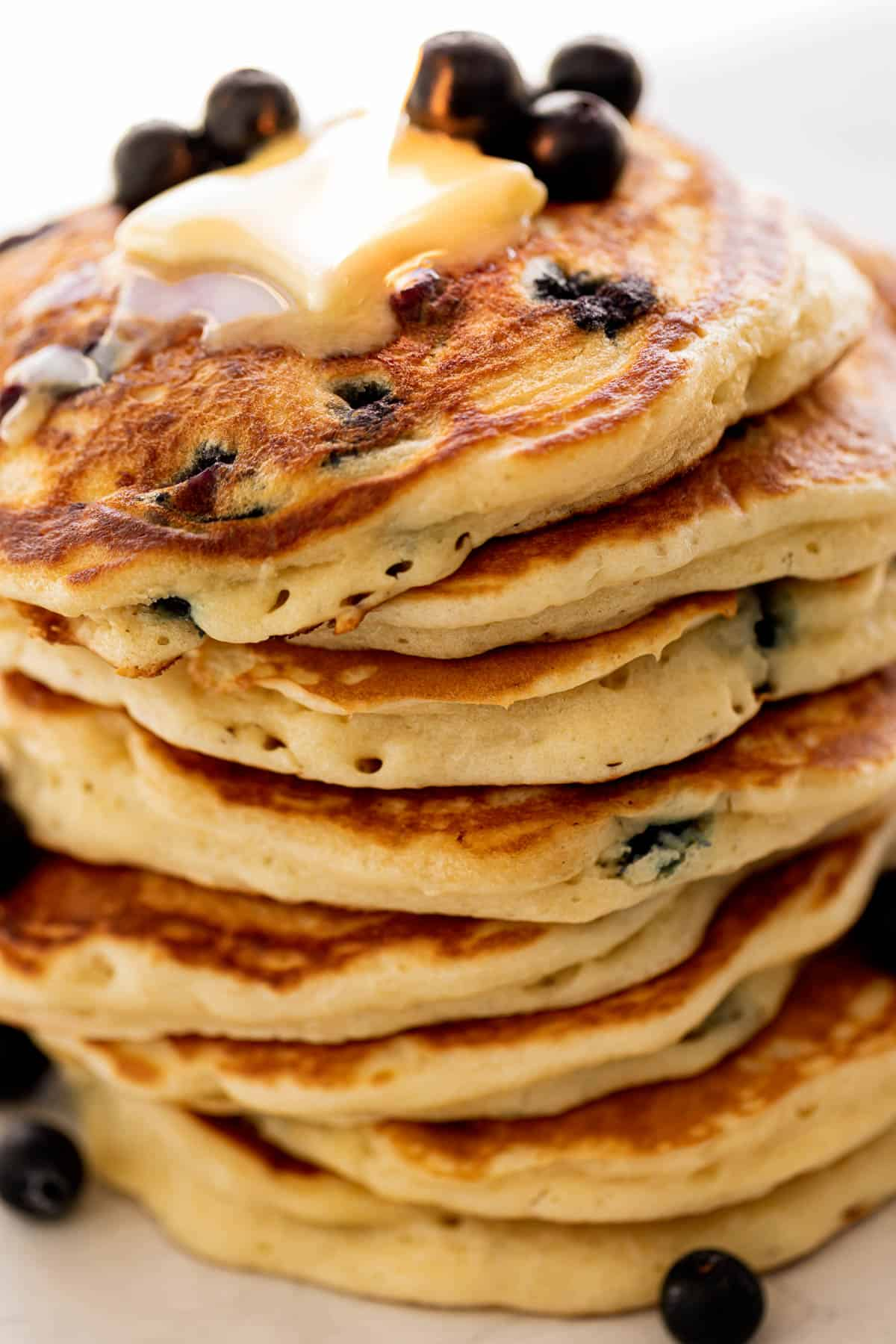 A stack of Blueberry Pancakes on a plate topped with fresh blueberries and melted butter | cafedelites.com