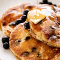 Three Blueberry Pancakes served on a plate with melted butter and maple syrup | cafedelites.com