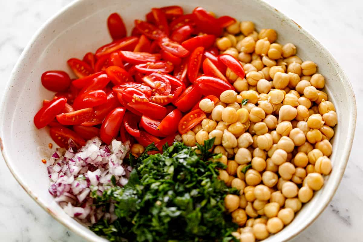 Ingredients piled in separate groups in a white bowl. From clockwise: cooked/canned chickpeas, chopped parsley, chopped red onion, quartered grape tomatoes | cafedelites
